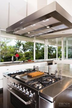 The cooker in this renovated kitchen is positioned at one end of a large island. It features a teppanyaki cooktop and a custom stainless steel surround, which accommodates oil and spice bottles.