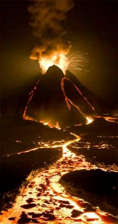 Erupting volcano with fire lit lava flow.