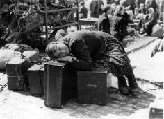 An exhausted Russian forced laborer takes a rest on luggage in April 1945 in Würzburg at a collection point for forced deported people. She was liberated by units of the 7th American army and waits for her repatriation.