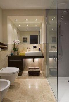 Baño decorado en tonalidades neutras y madera con baldosas de tamaño grande
