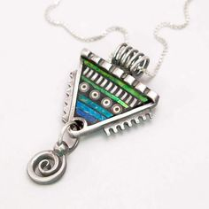 Silver triangle, twirl polymer pendant with iridescent inlay. $175.00, via Etsy.  ( Liz Hall )
