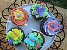 Chocolate cupcakes with a chocolate ganache filling and topped with vanilla buttercream and homemade fondant flowers and butterflies