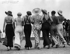A group of fashionable women sporting beach pajamas and huge straw hats on a British beach in 1934.