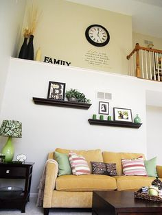 Kitchen:  Clock and decal for south vaulted ceiling wall, above cabinets. Living Room: Hanging of frame above the candles on shelf.