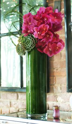 Bright pink vanda orchids with subtle succulents and curls of bear grass in a tall cylinder with banana leaves.