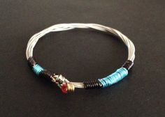 This is a handmade 3 string silver coloured guitar string bracelet bound with some black and turquoise wire. The bracelet is stackable. Very unique, suitable for men, women and teenagers.  Wear a piece of Manchesters rich music heritage with our recycled guitar string Bangles. We source all our strings from Manchesters leading music store which is frequently used by famous musicians on the manchester music scene. Who knows who would have used the strings we make our products with. All our…