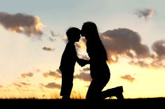 Mother Lovingly Kissing Little Child at Sunset stock photo