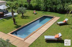 Un Couloir de nage de la gamme Cn de Piscinelle. Implantée au milieu d'une pelouse avec un simple accès par une bande de terrasse en ipé. Une piscine résolument contemporaine !
