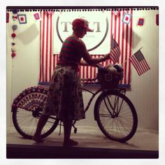 4th of July Window Display In Pictures - photo by Anna Dianich of Tolt Yarn & Wool me working on the finishing touches of our yarn bombed vintage Schwinn for a 4th of July Yarn shop window display.
