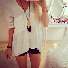 necklace, oversized top and shortie black lace shorts