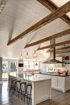 Ranch Cottage with Transitional Coastal Interiors. The kitchen feels spacious with its beamed cathedral ceiling and double islands.