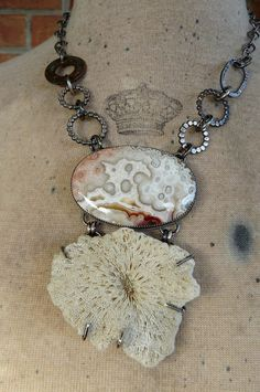 This beautiful piece is made with two striking summery elements that remind me of long days and warm sand. The top stone is a crazy lace agate measuring 2 inches wide by 1 3/8 inches and contains warm hues of orange, white, red and tan. the clarity of the design is what makes this stone a show stopper. The bottom natural, ivory sponge coral is 2 3/8 wide by 1 7/8. Both are set in sterling silver. The chain is a mix of sterling silver links and an antique coin. The entire piece ...