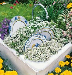 An old sink framed with wood and painted. Then they added dirt, a real faucet, real dishes, then planted flowers for the bubbles!