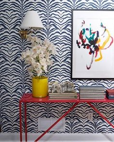 For wallpaper that has a heavy pattern, a good thing to hang is abstract art: it adds color, dimension, and interest to the walls without the worry of details or subject losing to it's competing surrounding