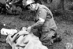 Normandy, 1944. An American medic from the 82nd US Airborne Div lights a cigarette for a wounded German prisoner.