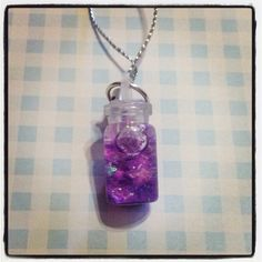 A little glass jar/bottle charm, with purple glitter and stars floating in it! The jar is filled with mineral oil, so when it is shaken, the glitter, polymer stars and confetti in it will float gently around. The jar is made out of glass, and the stopper is rubber and is sealed with glue.  Make...