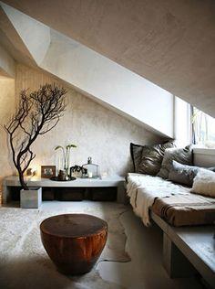 コンクリート打ちっぱなしの空間に素朴なベンチと、敷物をしいたナチュラル空間です。コンクリートの壁に柔らかく反射する陽ざしを楽しみながら、くつろげるリビング。