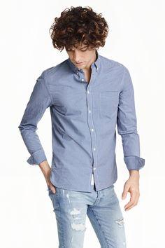 Camisa de algodón: Camisa de manga larga en tejido lavado de algodón. Modelo con cuello americano, un bolsillo superior y canesú con trabilla en la espalda. Corte estándar.