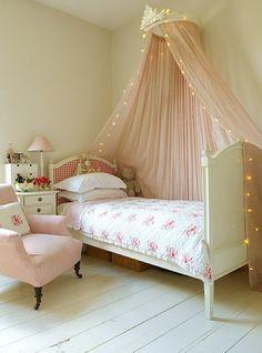 un lit mignon et ciel de lit bébé rose avec éclairage
