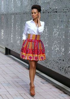 I love that she is wearing an African print skirt with a crisp white shirt and strappy sandals.