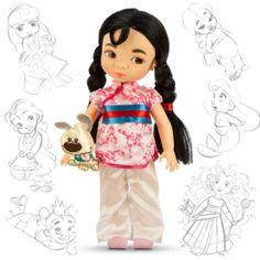 """Bevor sie zur mutigen Kriegerin wurde, war Mulan ein kleines Mädchen wie jedes andere! Die Disney-Künstler haben diese Puppe mit tollen Details gestaltet. Sie hat langes Haar, trägt eine Satintunika und hat ein """"Kleiner Bruder""""-Kuscheltier bei sich."""