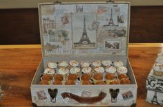 Instead of a cake, we did small cupcakes for the party.  I placed them in a Paris theme box from Michaels.  They are sitting on a cardboard box covered in tissue paper to raise them up for easier grabbing.  The birthday girl's cup cake was placed on a smaller Paris themed box beside the suitcase.