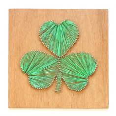Create a St. Patrick's Day shamrock with plywood, linoleum nails and twine.
