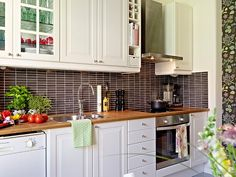 Kitchen tiles, wood counters and white cupboards.