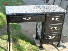 A cute vanity table refinished using spray paint and wrapping paper.