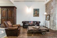 Canapé Chesterfield, fauteuil club, vieux parquets en bois, table basse à roulettes, armoire ancienne, mur pierres apparentes...