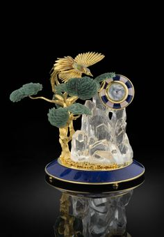 Luxury Table Clock. Soaring phoenix pavé with semi-precious stones. Bonzai tree carved out of green aventurine. Rock crystal mountain mounted on blue lapis lazuli base.By Royal Insignia.