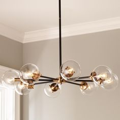 """Urban Globe Radial Chandelier - 8 Light A mid century modern design with clear globes radiating out from a center spoke in a combination of matte black and antique gold metals. (12-46""""OAH x 36""""Dia). 8 x 60W max candelabra sockets."""
