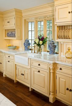 """What a sophisticated """"country-style kitchen""""!  That window is gorgeous and the sink & faucet ROCKS!!  Love the stunning blue dishes/jars against that soft, buttery yellow cabinetry, warm wood floors and bright white countertops."""
