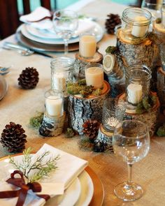 Round tables will have tree stumps, candles in glass, votives, a cylinder with submerged woodsy elements and floating candle, and a small low flower arrangement in a woodsy container, or a small fern or other woodsy plant. Moss and jeweltone flowers to be tucked in and around, as well as pinecones (provided by clients). Fabric under stumps to protect venue's linens.