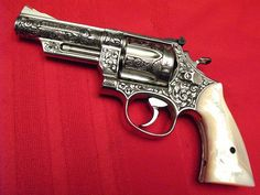 """Smith & Wesson Model 57, .41 Magnum, 4-inch barrel, pinned & recessed revolver.  Gun was hand engraved by the late Ben Shostle in 1998. This revolver has beautiful deep relief cut engraving in a classic floral pattern. The revolver was given a """"French Coin"""" finish.  Custom action work performed by Paul Sallee. The action was tuned, the barrel ported, hammer skeletonized, & an extra ball detent added to the crane. Grips are genuine mother-of-pearl."""