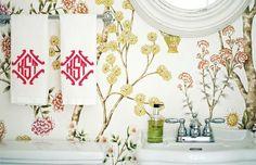 Monogram guest towels against a pretty floral wallpaper