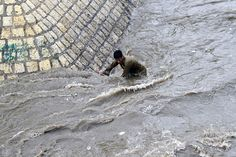 A boy tries to get out of a flooded street following heavy rains in Sanaa