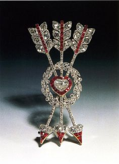 Cupid's arrows set with rubies and diamonds, piercing a ruby-set diamond heart. This brooch dates from circa 1900.