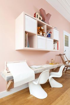 Pastel pink walls in living room with children's toys storage
