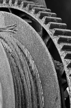 A black and white photograph of an old piece of machinery with rusted cable and gears. To purchase please go to http://memoriesoflove.imagekind.com