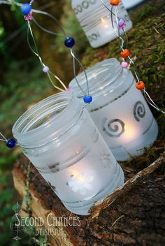 Frosted glass lanterns. Decorate recycled jars with rubber bands and stickers and then spray with frosted spray. Stick t-lights inside and add the beaded and wired handle.