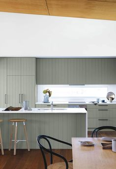 In this serene designer Macmasters Beach house the old cupboards were replaced with shiplap cabinetry painted in Dulux Tarzan Green for a nature-inspired look. The shiplap adds a striking visual feature to the kitchen area, and the green complements the natural materials and tones in the home beautifully.