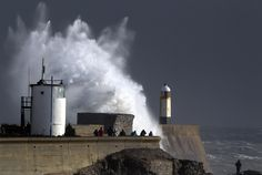 People take photographs of waves crashing against the harbor wall on Jan. 3 in Porthcawl, Wales. High winds gusting up to 95mph and heavy rain have been affecting many parts of the country disrupting travel and causing damage to buildings. (Matt Cardy/Getty Images)