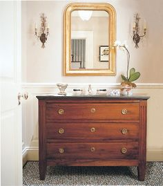 louis gilded mirror above antique dresser as sink