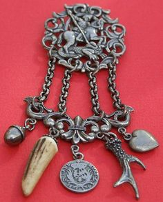Antique Silver Plated Chatelaine With A Land Munz Medal Or German Coin Dating 1803. The Chatelaine Clip Features A Scene Of A Knight Which May Be George Fighting A Dragon, Having A Hunting Theme, The Attachments Featuring A Puffy Acorn Charm, A Real Animals Tooth, A Silver Deer Antlers And Silver Puffy Heart Charm, With The Lower Part Of The Chatelaine Depicting A Fleur de Lis - Paris, France   c.1880