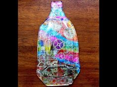 SLUMPED GLASS BOTTLES - YouTube - by Chewysmum (she has lots). This one is made with sticky adhesive and materials adhered to the back of the bottle.