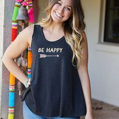 "BE HAPPY Sleeveless Hangout Tee - This charcoal sleeveless hangout tee is so cute and comfy! It features the inspiring sentiment, ""Be happy"" with gold foil details and a colorful arrow. The raw edge scoop neck and gentle swing adds movement and an incredibly flattering fit!"