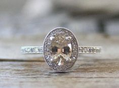 Beautiful white gold diamond halo engagement ring featuring a rare natural oval cut champagne peach sapphire measuring x 5 mm and weighing ct. Peach Sapphire Rings, Sapphire Diamond, White Sapphire, White Gold Diamonds, Halo Diamond Engagement Ring, Engagement Rings, Tiny Rings, Fine Jewelry, Jewellery