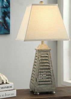 Create a captivating beach cottage style with this 28.5 inch tall resin antique grey washed shutter table lamp.