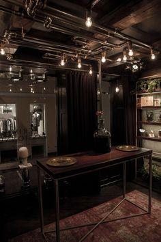 Crime Passionnel niche perfume boutique interior design. Pipe light, rebar table, aged carpet.